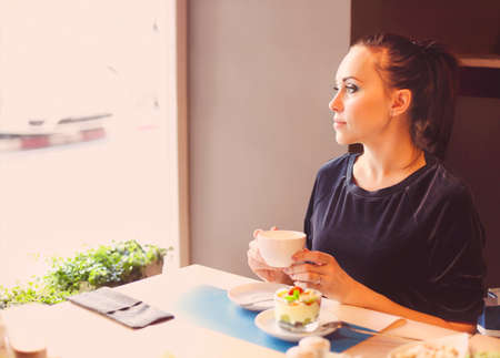 dof: Beautiful young woman drinking tea in cafe and looking to the window. Shallow depth of field