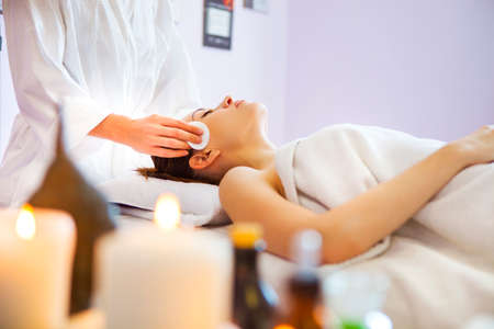 Relaxed woman with a deep cleansing nourishing face mask applied to her face. Spa treatment 스톡 콘텐츠