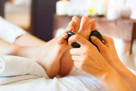 massager: Massage of female foot in spa salon. Healthy lifestyle and relaxation concept. Close up Stock Photo