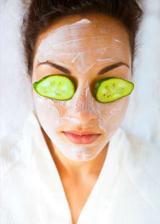 woman eye: Young happy woman with a facial mask and cucumber on her face Stock Photo