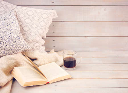 Cozy still life with book, coffee, pillows and plaid on the light wooden background. Close up 스톡 콘텐츠