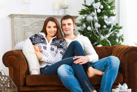 young tree: Young happy couple sitting on the sofa by Christmas tree