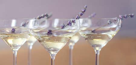 delicatessen: Glasses of champagne decorated with lavender on blurred background
