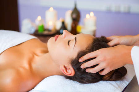 Close up portrait of a young woman getting spa treatment. Head massage