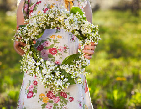 Little girl holding wreath from lily of the valley in her hands
