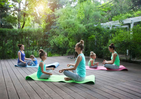 mothers group: Group of mothers and daughters doing exercise practicing yoga outdoors. Healthy lifestyle Stock Photo