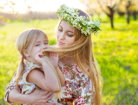 mommy: Happy mother and her little daughter in the spring day in a blossoming garden