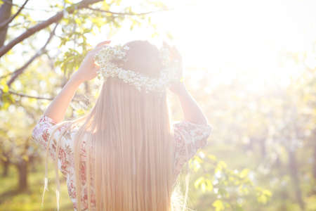 Beautiful romantic woman with long blond hair in a wreath of apple trees in the spring garden
