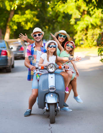 Happy young family riding a vintage scooter in the street wearing hats and sunglasses. Holiday and travel concept