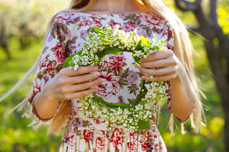 Young woman holding wreath from lily of the valley in her hands. Close up Stock Photo