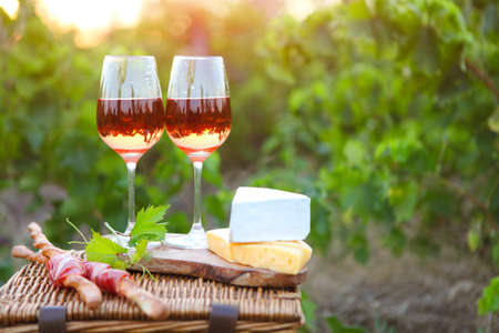 Two glasses of rose wine with bread, meat, grape and cheese on the vineyard background Stockfoto