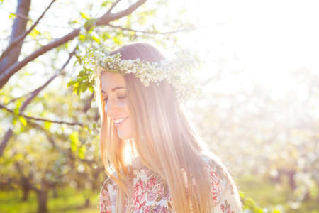 Beautiful romantic woman with long blond hair in a wreath of lily of the valley in the spring garden Stockfoto