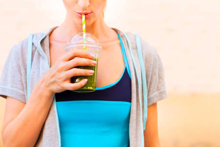 Woman drinking vegetable smoothie after fitness running workout on summer day. Fitness and healthy lifestyle concept