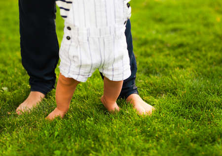 mother helping baby: Baby boy taking first steps and mother helping in summer garden