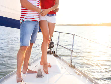 rich people: Feet of a couple on sailboat deck in the sea. Sunset Stock Photo