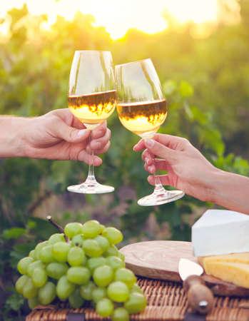 bebiendo vino: feliz pareja joven que goza de unas copas de vino blanco en el vineeard