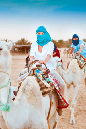 poorness: Young caucasian woman tourist riding on camel in Sahara desert. Tunis
