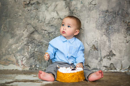 smashing: First birthday cake smashed by baby boy. Adorable baby smashing cake Stock Photo