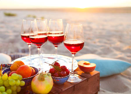 Glasses of the red wine on the sunset beach picnic 免版税图像