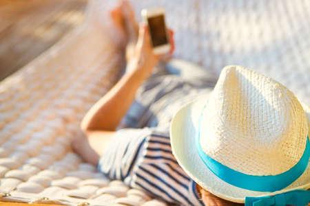 게으른 시간. 여름 하루에 휴대 전화와 해먹에서 모자에 남자