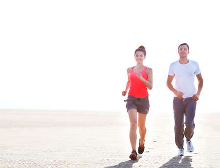 Portrait of couple jogging outside, runners training outdoors working out in nature against blue sky with sunset light