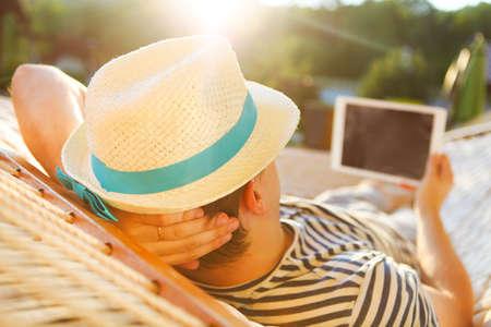 perezoso: Momentos de pereza. Hombre en el sombrero en una hamaca con el ordenador tableta en un día de verano