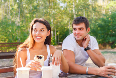 huddling: Man and woman or young couple drinking coffee and sitting in city park in summer Stock Photo