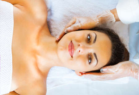 Close up portrait of a young woman getting spa treatment. Face massage Imagens