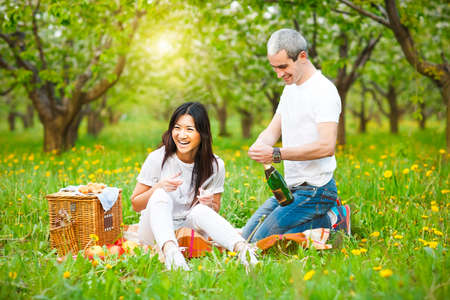 asian lifestyle: Happy smiling couple drinking champagne at picnic in the spring park Stock Photo