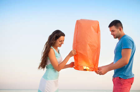 red sky: Young couple start a red Chinese sky lantern in the dusk near the sea