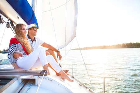joven sonriente pareja en un barco de vela en la puesta del sol del verano Foto de archivo