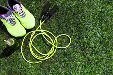 Running shoes, jump rope and drink bottle with green juice on grass background