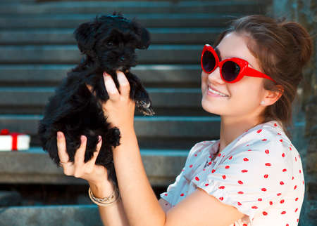 lap dog: Young brunette woman hugging her lap dog puppy. Retro style