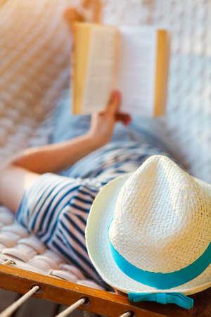 personas leyendo: Momentos de pereza. El hombre en el sombrero en una hamaca con el libro en un día de verano Foto de archivo