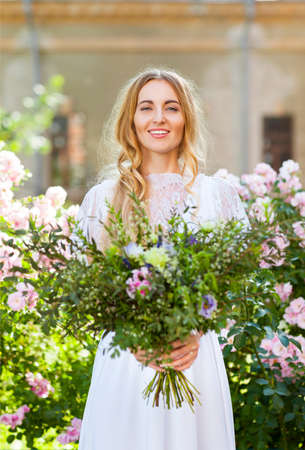 squaw: Happy bride with beautiful wedding bouquet of flowers in the style of boho Stock Photo