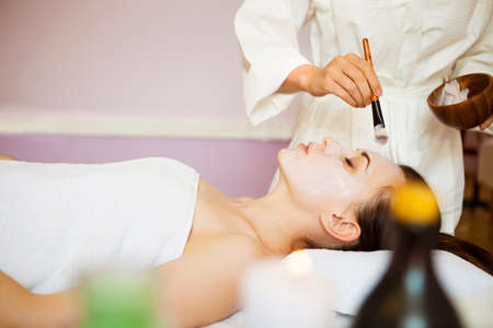 white mask: Young beautiful woman in a mask for the face of the therapeutic white mud. Spa treatment