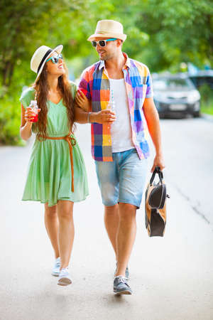 holiday spending: Happy couple walking with guitar drinking juice spending carefree time together. Travel, love and holiday concept