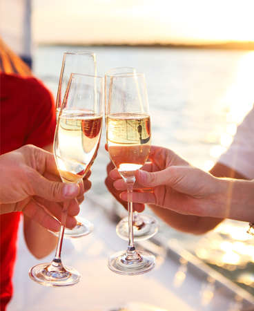 SPARKLING WINE: Happy friends with glasses of champagne on yacht. Vacation, travel, sea and friendship concept. Closeup. Stock Photo