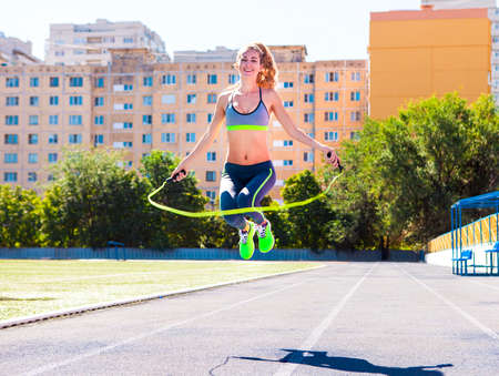 woman rope: Woman with jumping rope. Beautiful young woman with a jumping rope in her hands with a stadium as background