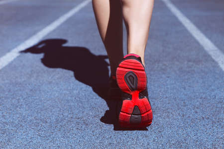 jogging: Athlete runner feet down stadium track. Closeup on female shoe and legs. Woman summer fitness workout. Jogging, sport, healthy active lifestyle concept.