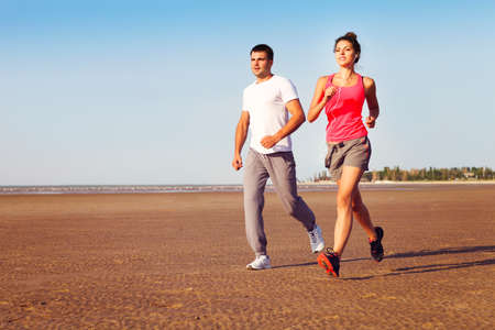 sexy couple on beach: Portrait of couple jogging outside, runners training outdoors working out in nature against blue sky