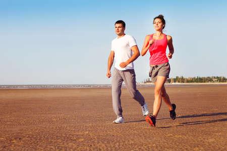 personas saludables: Retrato de pareja jogging exterior, la formación corredores trabaja al aire libre en la naturaleza contra el cielo azul
