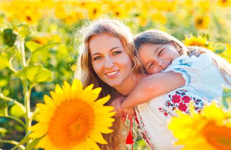 personas saludables: Feliz madre y su pequeña hija en el campo de girasol. Verano divertido