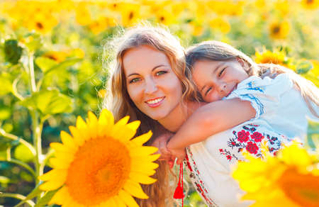 Happy mother and her little daughter in the sunflower field. Summer fun