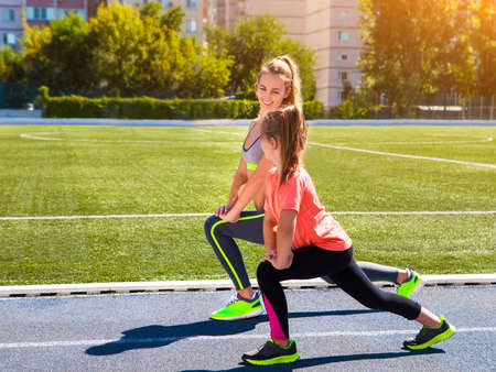 Mutter und kleine Tochter tun Übung im Stadion. Familie macht Fitness-im Stadion. Gesunde Familienkonzept