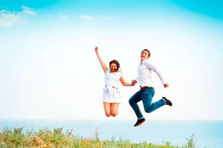 brincando: Joven pareja feliz saltando en las manos de playa que sostiene