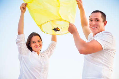 sky lantern: Young couple start a yellow Chinese sky lantern in the dusk near the sea