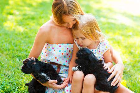 personas abrazadas: Niña linda y su madre abrazando a los cachorros de perro. La amistad y el concepto cuidado