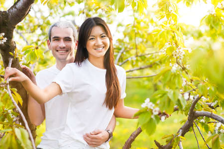 bloomy: Happy smiling couple in love in bloomy spring garden