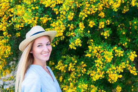 mimosa: Portrait of a beautiful young woman in the hat with mimosa flowers background Stock Photo